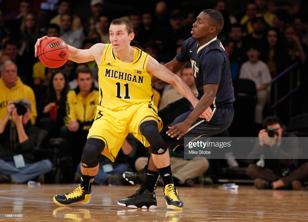 Nik Stauskas #11 of the Michigan Wolverines drives the ball towards the net against Tray Woodall #1 of the Pittsburgh Panthers during the NIT Season Tip-Off at Madison Square Garden on November 21, 2012 in New York City. Michigan defeated Pittsburgh 67-62.