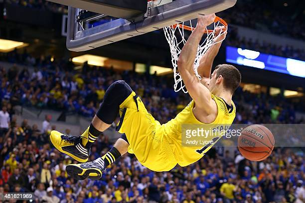 Nik Stauskas of the Michigan Wolverines dunks the ball over Dominique Hawkins of the Kentucky Wildcats in the second half during the midwest regional...