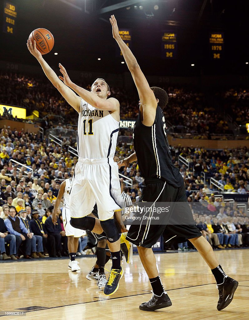 Nik Stauskas #11 of the Michigan Wolverines gets off a half shot over A.J. Hammons #20 of the Purdue Boilermakers at Crisler Center on January 24, 2013 in Ann Arbor, Michigan.