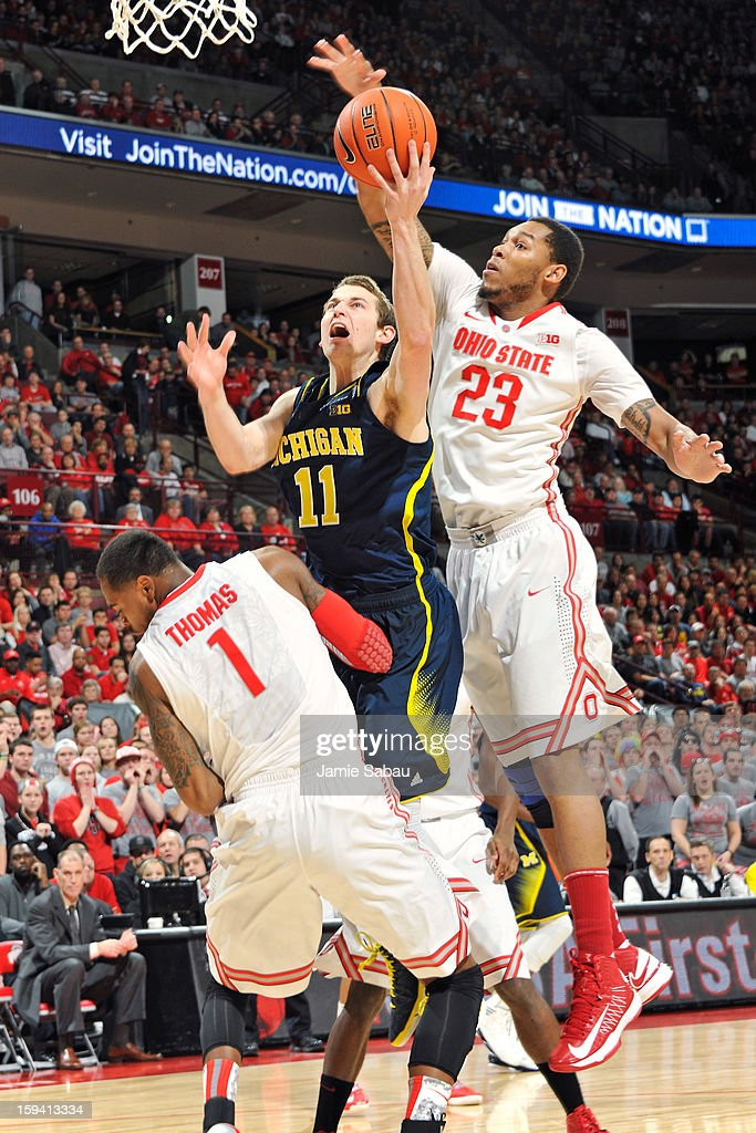 Nik Stauskas #11 of the Michigan Wolverines is called for a player control foul as he goes over Deshaun Thomas #1 of the Ohio State Buckeyes in the first half while Amir Williams #23 helps defend on January 13, 2013 at Value City Arena in Columbus, Ohio.