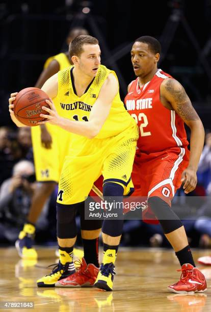Nik Stauskas of the Michigan Wolverines is defended by Lenzelle Smith Jr #32 of the Ohio State Buckeyes during the second half of the Big Ten...