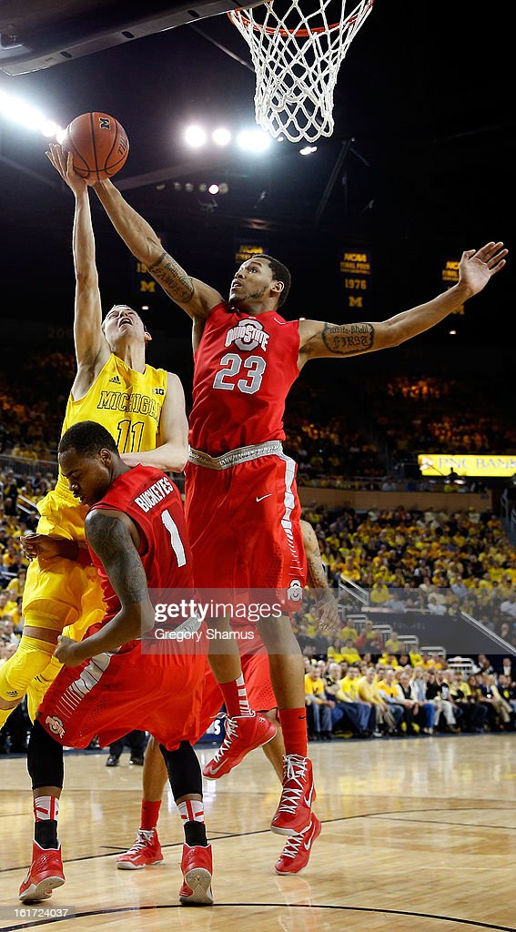 Nik Stauskas #11 of the Michigan Wolverines tries to drive the basket between Amir Williams #23 and Deshaun Thomas #1of the Ohio State Buckeyes but is called for a charge in the first half at Crisler Center on February 5, 2013 in Ann Arbor, Michigan.