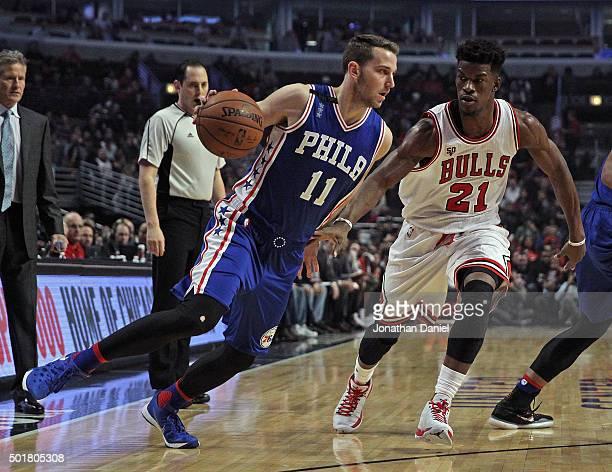 Nik Stauskas of the Philadelphia 76ers dirves against Jimmy Butler of the Chicago Bulls at the United Center on December 14 2015 in Chicago Illinois...