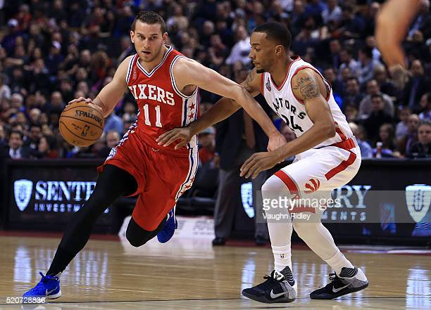 Nik Stauskas of the Philadelphia 76ers dribbles the ball around Norman Powell of the Toronto Raptors during the first half of an NBA game at the Air...