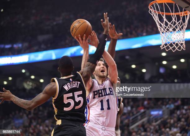 Nik Stauskas of the Philadelphia 76ers is fouled by Delon Wright of the Toronto Raptors as he goes to the basket during NBA game action at Air Canada...