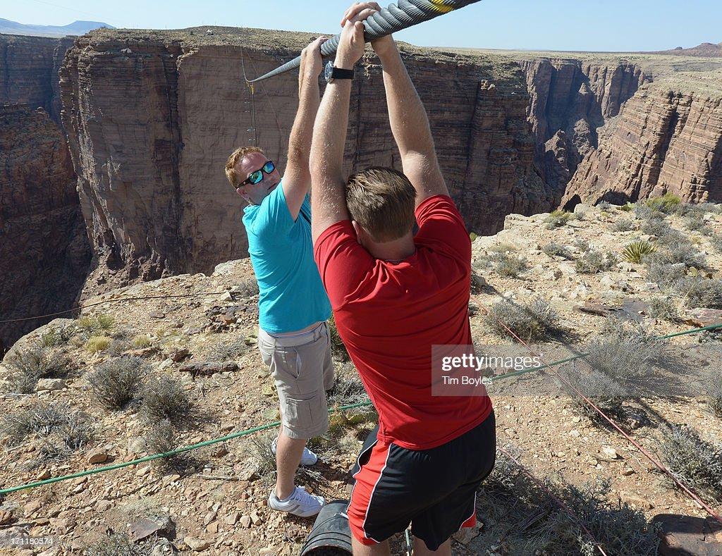 <a gi-track='captionPersonalityLinkClicked' href=/galleries/search?phrase=Nik+Wallenda&family=editorial&specificpeople=7696638 ng-click='$event.stopPropagation()'>Nik Wallenda</a> (R) and Mike Duff (L) hang on the wire during a training session before his historic high wire walk over the Grand Canyon at The Grand Canyon on June 22, 2013 in Grand Canyon, Arizona.