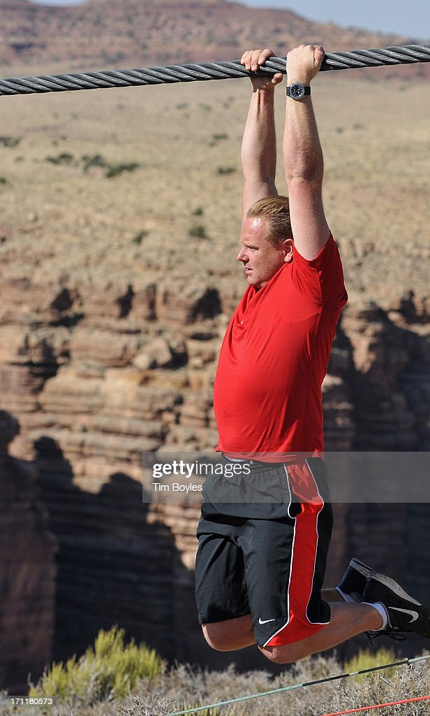 <a gi-track='captionPersonalityLinkClicked' href=/galleries/search?phrase=Nik+Wallenda&family=editorial&specificpeople=7696638 ng-click='$event.stopPropagation()'>Nik Wallenda</a> hangs on the wire during a training session before his historic high wire walk over the Grand Canyon at The Grand Canyon on June 22, 2013 in Grand Canyon, Arizona.