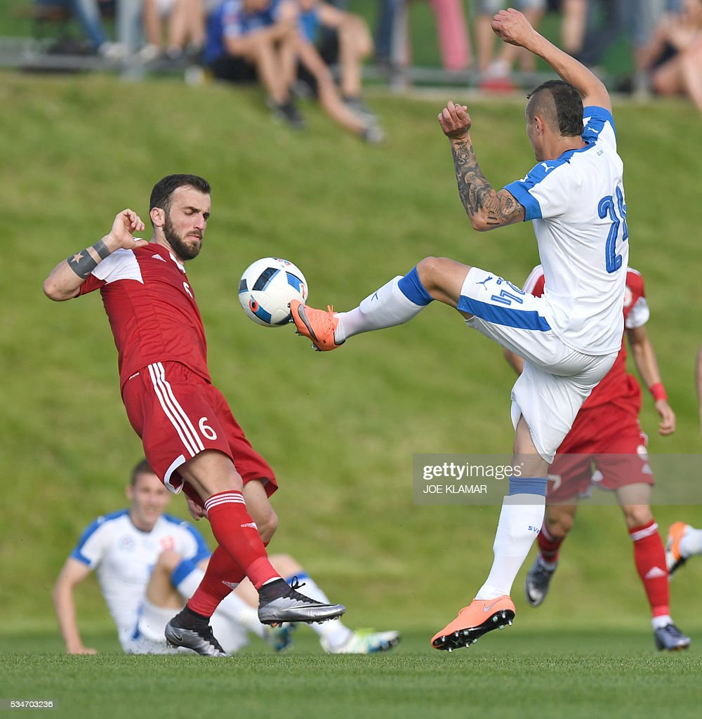 Nika Kvekveskiri of Georgia (L) and Slovakia's Adam Zrelak vie for a ball during their friendly match between Slovakia and Georgia in Wels, Austria on May 27, 2016. / AFP / JOE