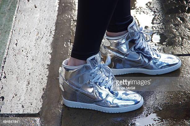 Nike 'Dunk Sky Hi' Metallic Silver Hidden Wedge women's Sneaker Boot worn with black leggings on wet London street
