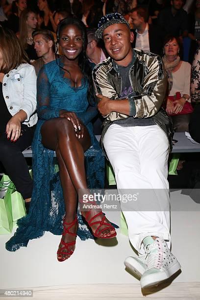Nikeata Thompson and Lou Bega attend the Ewa Herzog show during the MercedesBenz Fashion Week Berlin Spring/Summer 2016 at Brandenburg Gate on July...