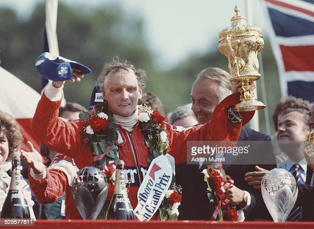 Niki Lauda of Austria and driver of the Marlboro McLaren International McLaren MP4B Ford Cosworth DFV V8 lifts the RAC Trophy and celebrates winning...