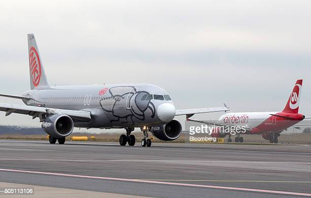A Niki Luftfahrt GmbH aircraft left taxis alongside an a passenger aircraft operated by Air Berlin Plc at Vienna International Airport operated by...