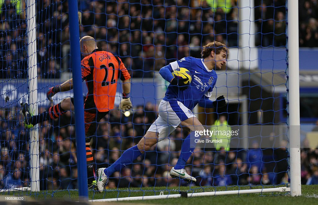 Nikica Jelavic of Everton runs out the goal with the ball as Aston Villa keeper Brad Guzan kicks the post in frustration after Marouane Fellaini of Everton has scored his teams second goal during the Barclays Premier League match between Everton and Aston Villa at Goodison Park on February 2, 2013 in Liverpool, England.