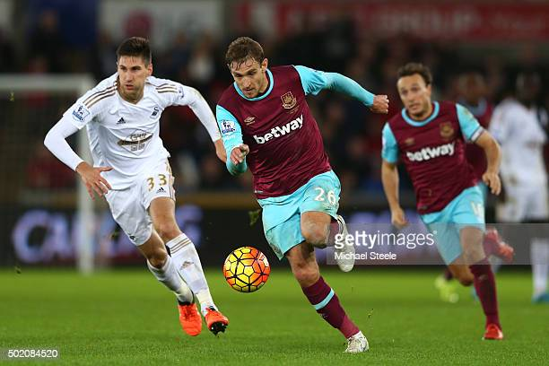 Nikica Jelavic of West Ham is pursued by Federico Fernandez of Swansea City during the Barclays Premier League match between Swansea City and West...