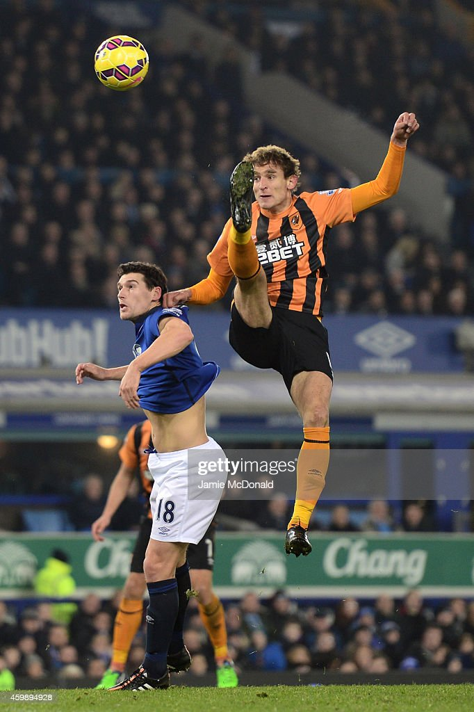 Nikica Jelevic of Hull City rises above Gareth Barry of Everton to strike the ball during the Barclays Premier League match between Everton and Hull City at Goodison Park on December 3, 2014 in Liverpool, England.