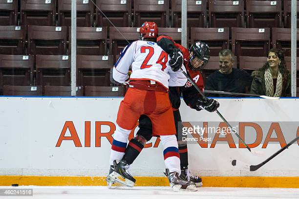 Nikita A Popugayev of Russia places a hit on Tyler Benson of Canada Black during the World Under17 Hockey Challenge on November 2 2014 at the RBC...