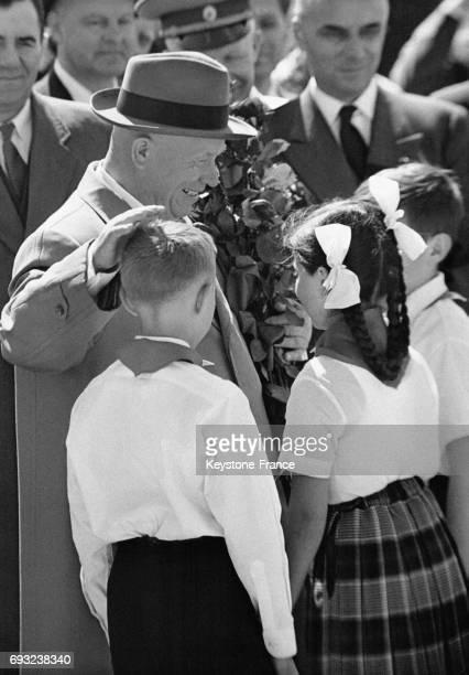Nikita Khrouchtchev au terme de sa visite à Paris caresse la tête d'enfants venus lui remettre des fleurs en guise d'adieu à l'aéroport avant son...