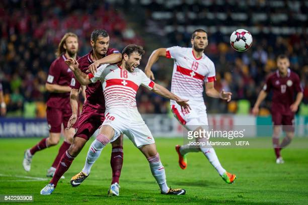 Nikita Kolesovs of Latvia competes with Admir Mehmedi of Switzerland during the FIFA 2018 World Cup Qualifier between Latvia and Switzerland at...