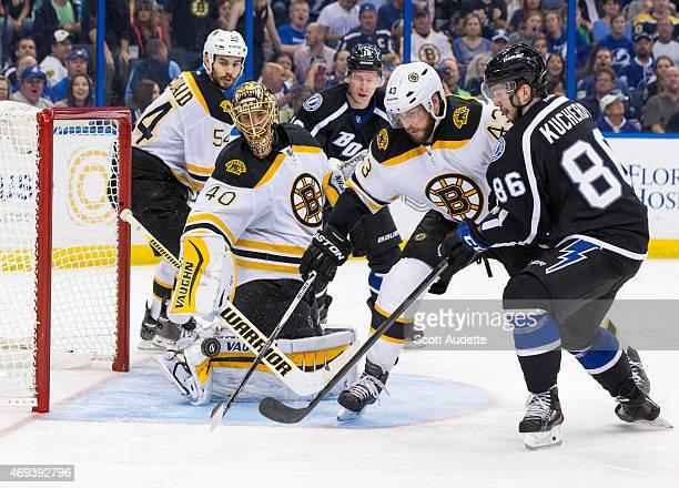 Nikita Kucherov of the Tampa Bay Lightning along with Matt Bartkowski and goalie Tuukka Rask of the Boston Bruins look for the puck during the third...