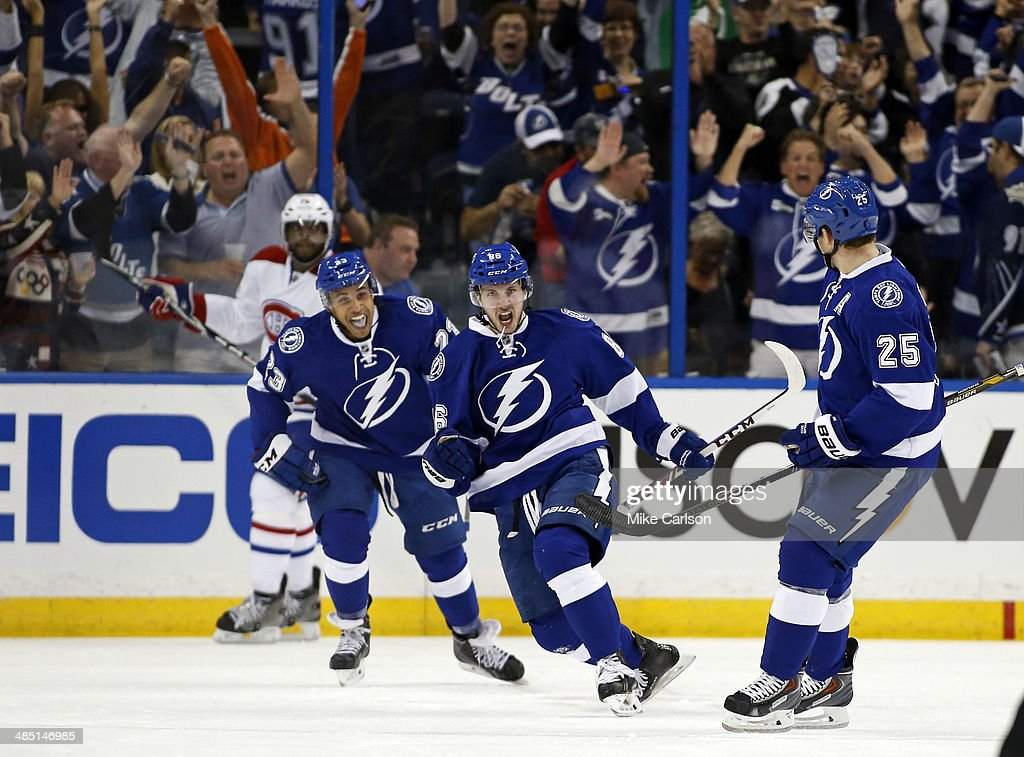 <a gi-track='captionPersonalityLinkClicked' href=/galleries/search?phrase=Nikita+Kucherov&family=editorial&specificpeople=7832285 ng-click='$event.stopPropagation()'>Nikita Kucherov</a> #86 of the Tampa Bay Lightning (C) celebrates his goal between teammates J.T. Brown #23 and <a gi-track='captionPersonalityLinkClicked' href=/galleries/search?phrase=Matt+Carle&family=editorial&specificpeople=582495 ng-click='$event.stopPropagation()'>Matt Carle</a> #25 as <a gi-track='captionPersonalityLinkClicked' href=/galleries/search?phrase=P.K.+Subban&family=editorial&specificpeople=714418 ng-click='$event.stopPropagation()'>P.K. Subban</a> #76 of the Montreal Canadiens reacts in Game One of the First Round of the 2014 Stanley Cup Playoffs at the Tampa Bay Times Forum on April 16, 2014 in Tampa, Florida.