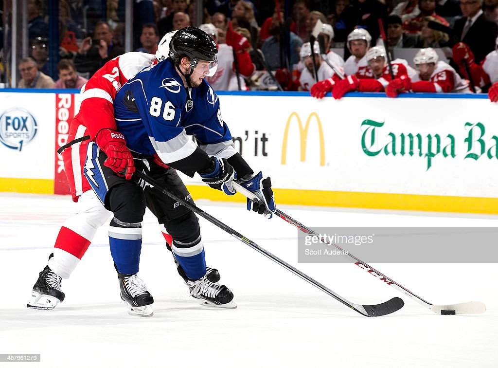 Nikita Kucherov #86 of the Tampa Bay Lightning controls the puck while getting hooked by <a gi-track='captionPersonalityLinkClicked' href=/galleries/search?phrase=Brian+Lashoff&family=editorial&specificpeople=5529056 ng-click='$event.stopPropagation()'>Brian Lashoff</a> #23 of the Detroit Red Wings during the third period at the Tampa Bay Times Forum on February 8, 2014 in Tampa, Florida.