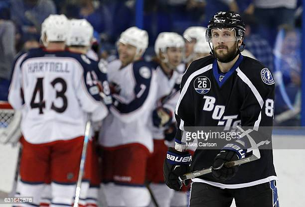 Nikita Kucherov of the Tampa Bay Lightning reacts as members of the Columbus Blue Jackets celebrate a win at the Amalie Arena on January 13 2017 in...