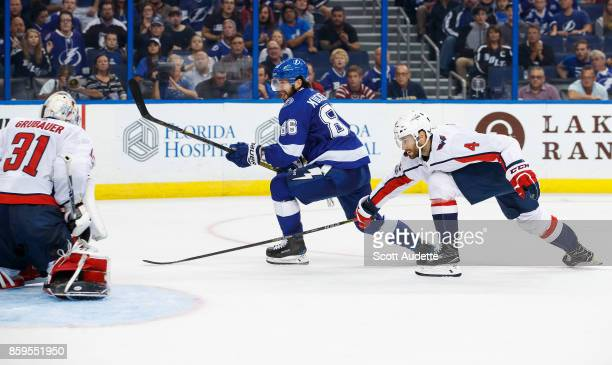 Nikita Kucherov of the Tampa Bay Lightning shoots the puck for a goal against goalie Philipp Grubauer and Taylor Chorney of the Washington Capitals...