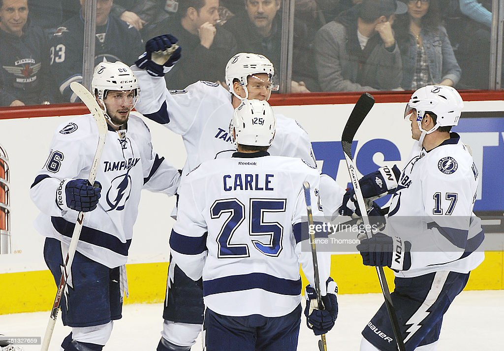 Nikita Kucherov #86, Ondrej Palat #18, Matthew Carle #25 and Alex Killorn #17 of the Tampa Bay Lightning celebrate a second period goal against the Winnipeg Jets at the MTS Centre on January 7, 2014 in Winnipeg, Manitoba, Canada.