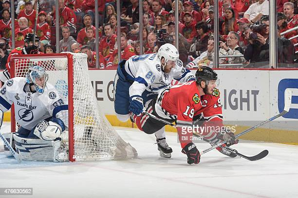 Nikita Nesterov of the Tampa Bay Lightning and Jonathan Toews of the Chicago Blackhawks fall behind goalie Andrei Vasilevskiy during Game Four of the...