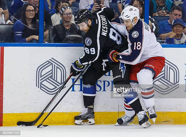 Nikita Nesterov of the Tampa Bay Lightning is tied up by Rene Bourque of the Columbus Blue Jackets during the first period at the Amalie Arena on...