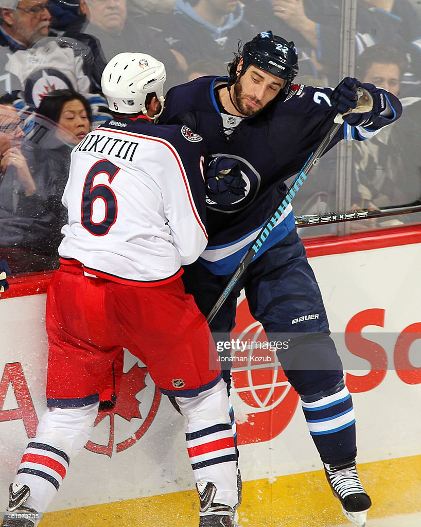 <a gi-track='captionPersonalityLinkClicked' href=/galleries/search?phrase=Nikita+Nikitin&family=editorial&specificpeople=722107 ng-click='$event.stopPropagation()'>Nikita Nikitin</a> #6 of the Columbus Blue Jackets collides with <a gi-track='captionPersonalityLinkClicked' href=/galleries/search?phrase=Chris+Thorburn&family=editorial&specificpeople=2222066 ng-click='$event.stopPropagation()'>Chris Thorburn</a> #22 of the Winnipeg Jets along the boards during third period action at the MTS Centre on January 11, 2014 in Winnipeg, Manitoba, Canada.