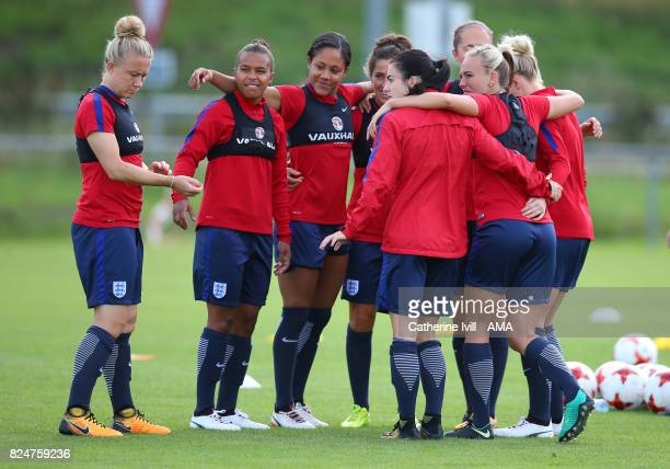 Nikita Parris and Alex Scott look over as the team wait for Laura Bassett of England Women to join the huddle during an England Women training...