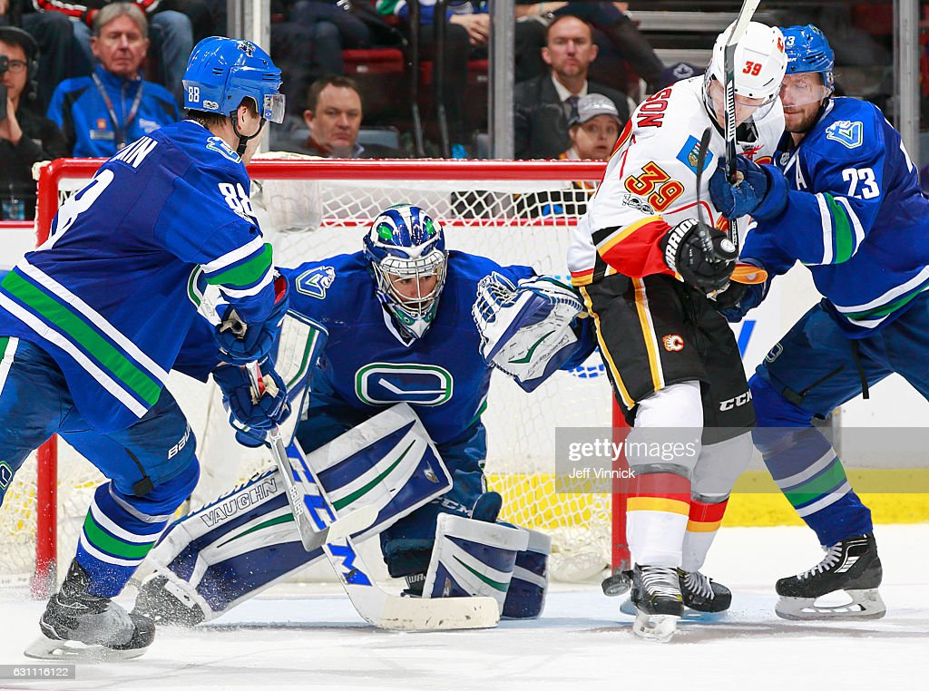 Nikita Tryamkin #88 and Alexander Edler #23 of the Vancouver Canucks and Alex Chiasson #39 of the Calgary Flames look on as Ryan Miller #30 of the Vancouver Canucks makes a save during their NHL game at Rogers Arena January 6, 2017 in Vancouver, British Columbia, Canada. Vancouver won 4-2.