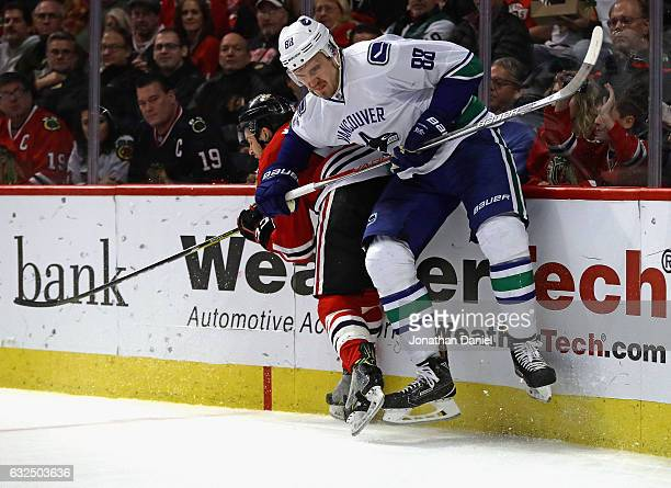 Nikita Tryamkin of the Vancouver Canucks checks Tanner Kero of the Chicago Blackhawks at the United Center on January 22 2017 in Chicago Illinois The...