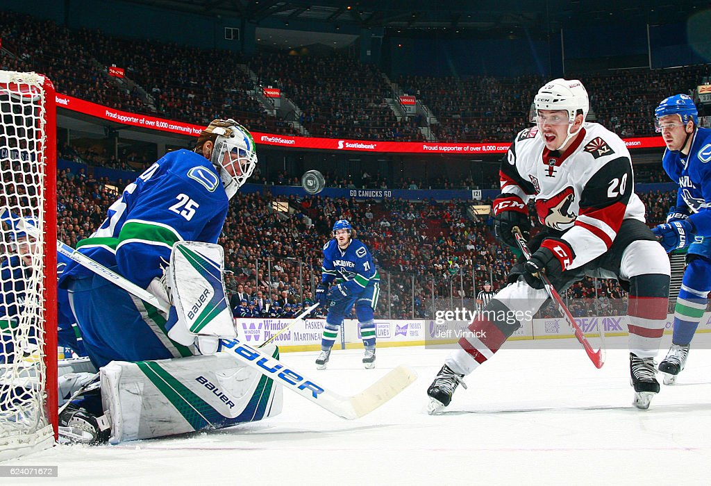 Nikita Tryamkin #88 of the Vancouver Canucks looks on as teammate Jacob Markstrom #25 makes a save off the shot of Dylan Strome #20 of the Arizona Coyotes during their NHL game at Rogers Arena November 17, 2016 in Vancouver, British Columbia, Canada. Vancouver won 3-2 in overtime.