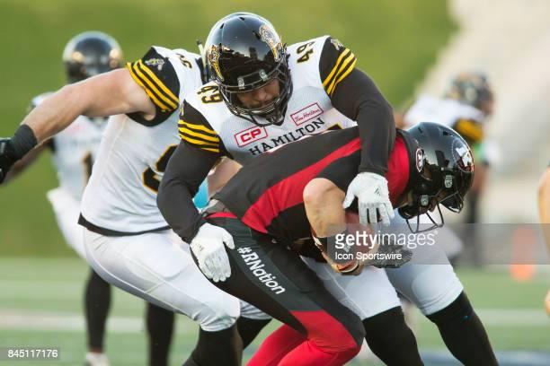 Nikita Whitlock of the Hamilton TigerCats sacks Ottawa Redblacks QB Trevor Harris on Ottawa's first possession in Canadian Football League Action at...