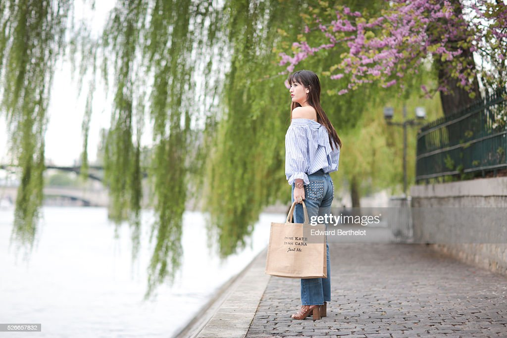 Nikita Wong (fashion blogger @meetmeinparee - Meet me in Paree), is wearing Diabless blue jeans, a Chicwish striped top, an Improbable bag with the inscription 'I'm not Kate, I'm not Cara, Just me', and Texto brown shoes, during a street style session, on April 30, 2016 in Paris, France.