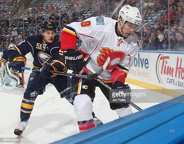 Nikita Zadorov of the Buffalo Sabres battles in the corner for the puck with Joe Colborne of the Calgary Flames at First Niagara Center on December...