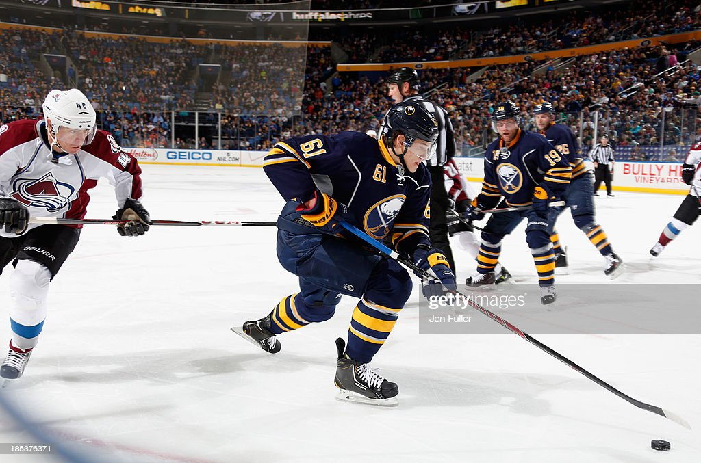 <a gi-track='captionPersonalityLinkClicked' href=/galleries/search?phrase=Nikita+Zadorov&family=editorial&specificpeople=9784875 ng-click='$event.stopPropagation()'>Nikita Zadorov</a> #61 of the Buffalo Sabres carries the puck during his first NHL game as he is followed by <a gi-track='captionPersonalityLinkClicked' href=/galleries/search?phrase=Alex+Tanguay&family=editorial&specificpeople=203231 ng-click='$event.stopPropagation()'>Alex Tanguay</a> #40 of the Colorado Avalanche at First Niagara Center on October 19, 2013 in Buffalo, New York. Colorado defeated Buffalo 4-2.