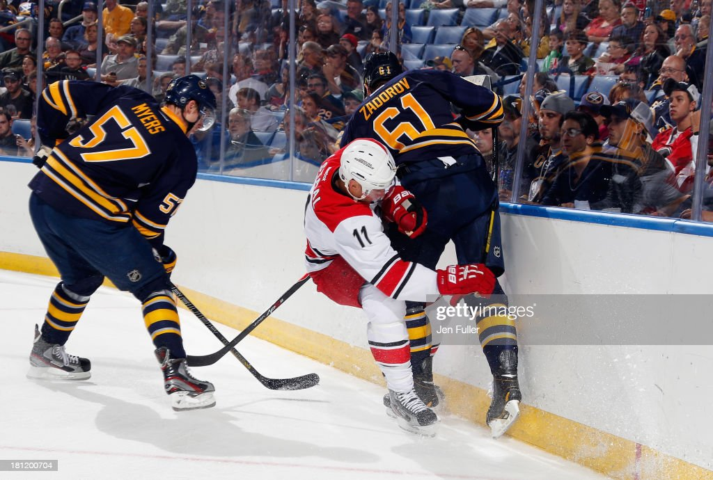 <a gi-track='captionPersonalityLinkClicked' href=/galleries/search?phrase=Nikita+Zadorov&family=editorial&specificpeople=9784875 ng-click='$event.stopPropagation()'>Nikita Zadorov</a> #61 of the Buffalo Sabres checks Jordan Stall #11 of the Carolina Hurricanes alongside teammate <a gi-track='captionPersonalityLinkClicked' href=/galleries/search?phrase=Tyler+Myers&family=editorial&specificpeople=4595080 ng-click='$event.stopPropagation()'>Tyler Myers</a> #57 in a preseason game at First Niagara Center on September 19, 2013 in Buffalo, United States.
