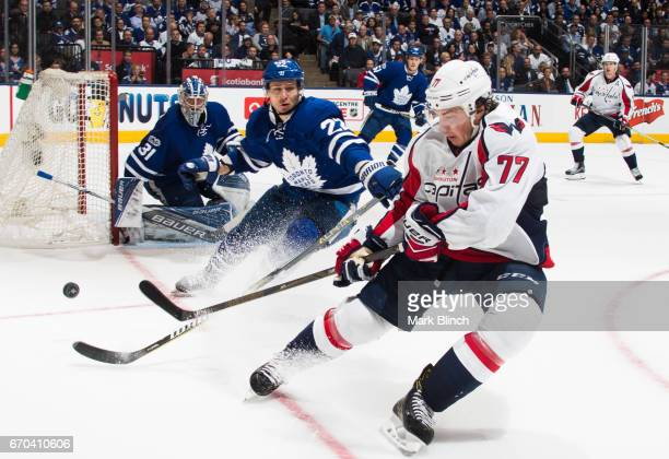 Nikita Zaitsev of the Toronto Maple Leafs and TJ Oshie of the Washington Capitals battle for the puck in front of Frederik Andersen of the Toronto...