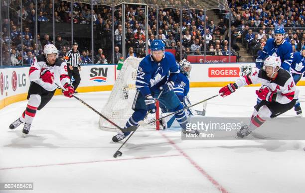 Nikita Zaitsev of the Toronto Maple Leafs battles for the puck with Taylor Hall and Adam Henrique of the New Jersey Devils during the second period...