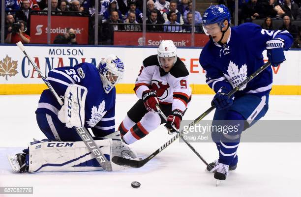 Nikita Zaitsev of the Toronto Maple Leafs clears the puck away from Taylor Hall of the New Jersey Devils and Curtis McElhinney of the Toronto Maple...