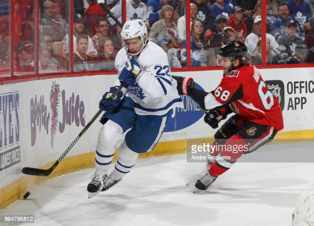 Nikita Zaitsev of the Toronto Maple Leafs controls the puck against Mike Hoffman of the Ottawa Senators behind the net at Canadian Tire Centre on...