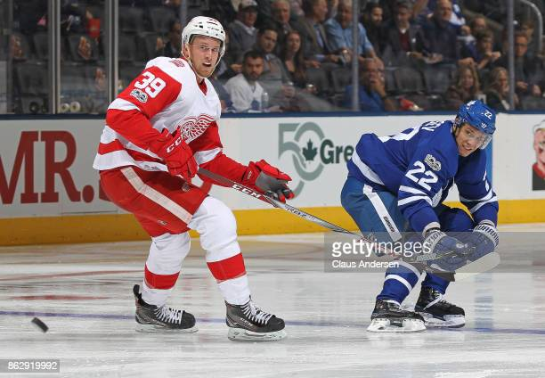Nikita Zaitsev of the Toronto Maple Leafs flips a puck past Anthony Mantha of the Detroit Red Wings in an NHL game at the Air Canada Centre on...