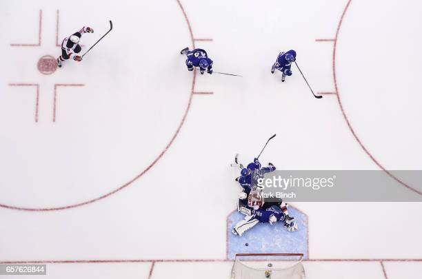 Nikita Zaitsev of the Toronto Maple Leafs upends Joseph Blandisi of the New Jersey Devils into Curtis McElhinney of the Toronto Maple Leafs resulting...