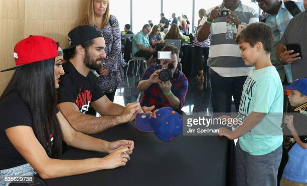 Nikki Bella and Seth Rollins greet a wish kid at the WWE Superstars Surprise MakeAWish Families at One World Observatory on August 19 2017 in New...
