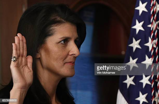 Nikki Haley raises her right hand while being sworn in as the US Ambassador to the United Nations January 25 2017 in Washington DC Haley was formerly...