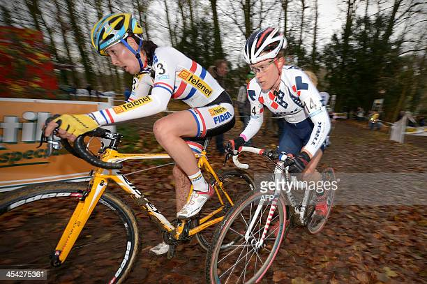 Nikki Harris of Britain and US Katie Compton compete during the Vlaamse Druivencross cyclocross cycling race in Overijse on December 8 2013 Compton...