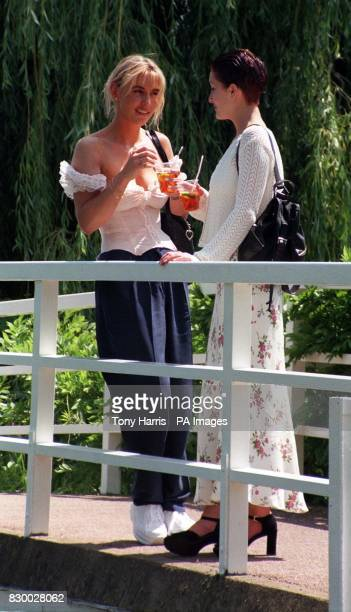 Nikki KerrMoller and Helen Brown enjoy a glass of Pimms in the warm London heat today on the bridge at the Hurlingham Garden Party the traditional...